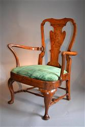 An early 18th century elm low elbow chair.