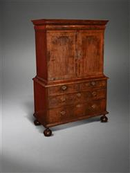 A Queen Anne walnut enclosed cabinet on chest.